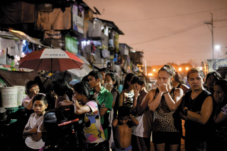 Onlookers at a crime scene under investigation by the SOCO (scene of crime operatives), Tondo, Manila, September 2016